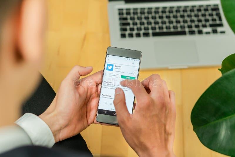 Ljubljana, Eslovenia 29 4 2019: smartphone de la tenencia del hombre de negocios y el intentar transferir el app de Twitter fotos de archivo