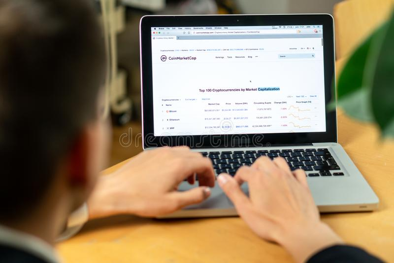 Ljubljana, Sloveni? 29 4 2019: zakenmanzitting bij bureau voorlaptop computers met financiële grafieken en royalty-vrije stock afbeelding