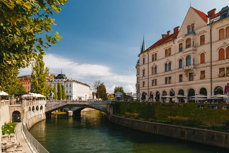 Ljubljana Slovenia, Wrzesień, -, 8 2018: Piękny widok przy rzecznym Ljubljanica, Cankarjevo Nabrezje i trójki mostem turysta zdjęcie royalty free
