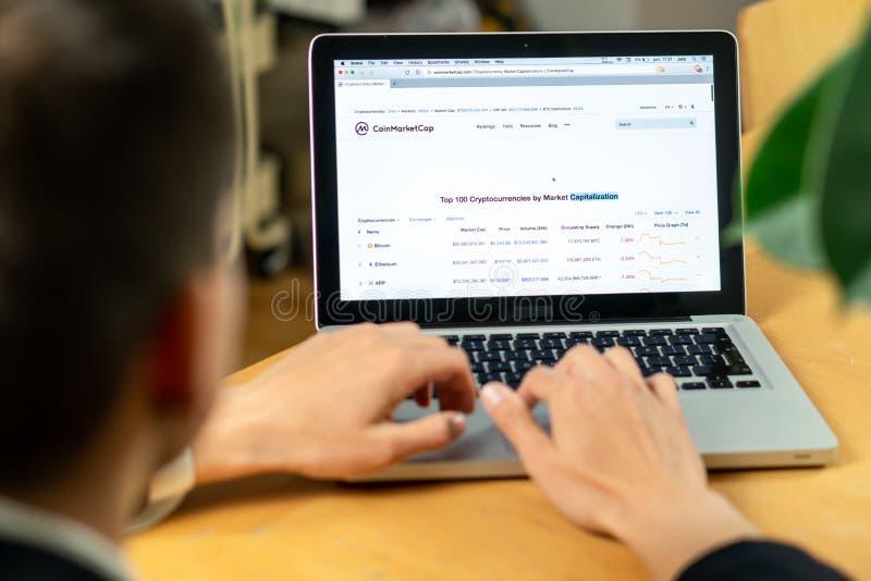 Ljubljana Slovenien 29 4 2019: affärsman som sitter på datorer för bärbar dator för kontorsskrivbord främre med finansiella grafe royaltyfri bild