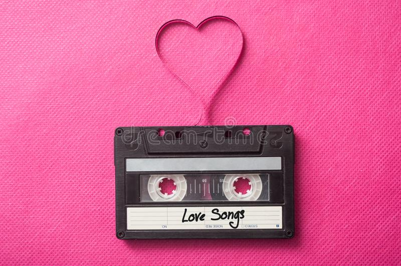 ljudkassett med text'förälskelsesånger med den magnetiska musikbandet i formad hjärta på rosa bakgrund fotografering för bildbyråer