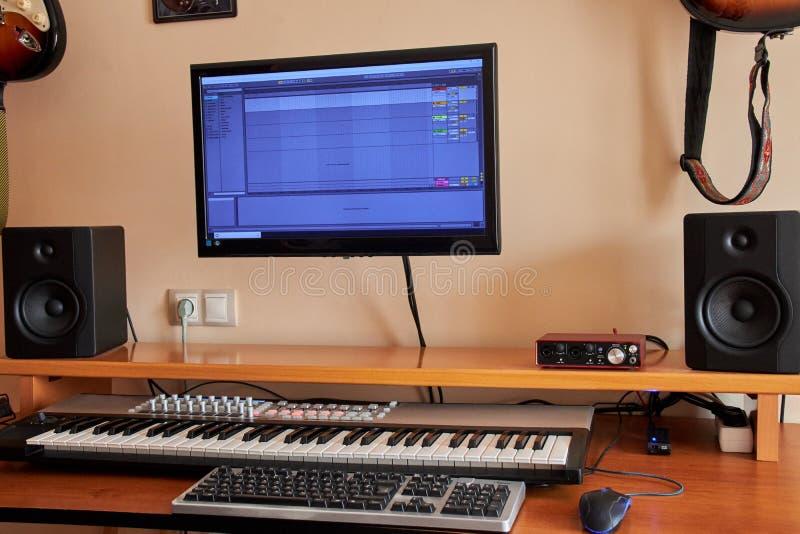 Ljudsignal hem- studio som utrustas med det midi tangentbordet, bildskärmar och det solida kortet royaltyfria foton