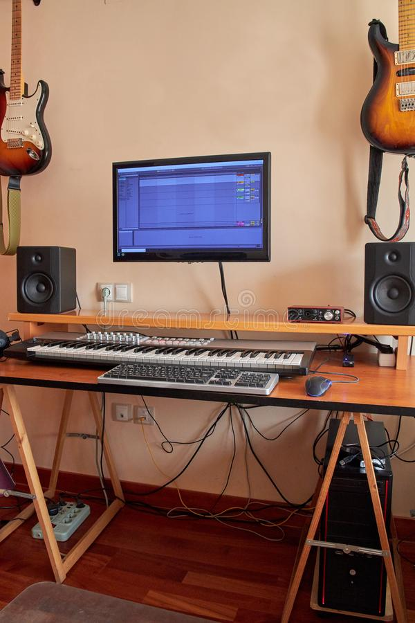 Ljudsignal hem- studio som utrustas med det midi tangentbordet, bildskärmar och det solida kortet arkivfoto