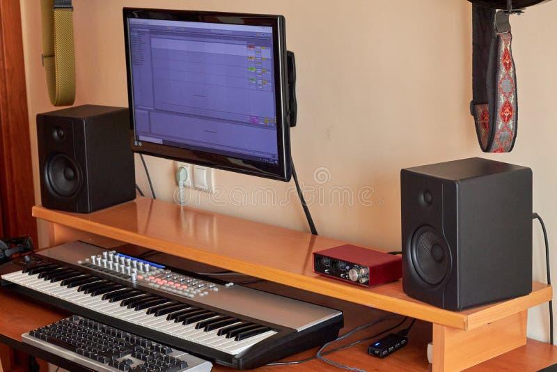 Ljudsignal hem- studio som utrustas med det midi tangentbordet, bildskärmar och det solida kortet royaltyfri foto