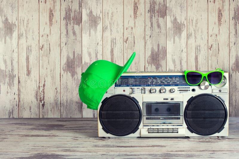 Ljudsignal spelare för tappning och trendigt kulört lock, solglasögon Begreppet av stilen för musikhöftflygtur royaltyfri foto