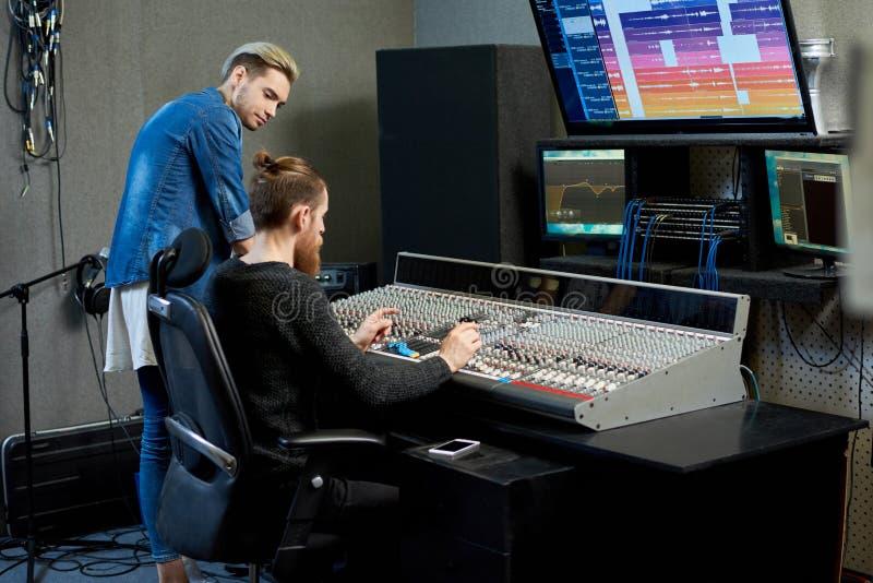 Ljudsignal tekniker som väljer ljud för spår samman med musiker fotografering för bildbyråer