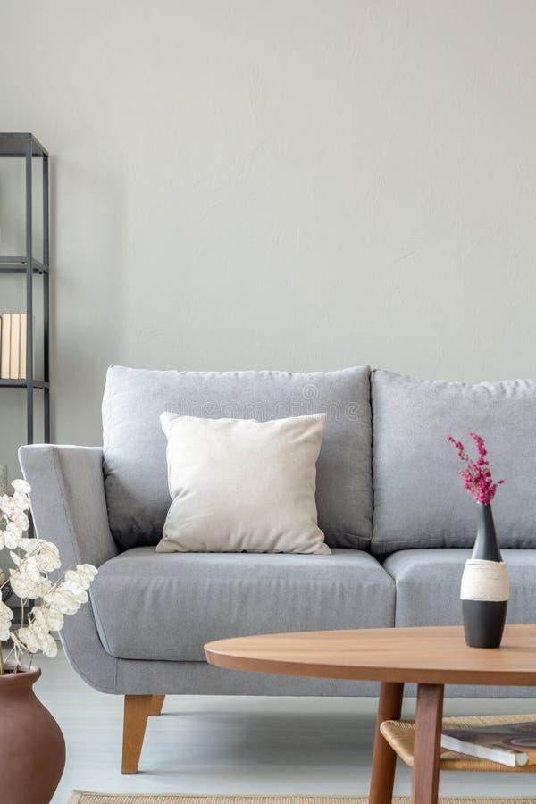 Ljung i vas på trätabellen bredvid den bekväma gråa soffan i monochromatic vardagsrum, verkligt foto med kopieringsutrymme royaltyfria foton
