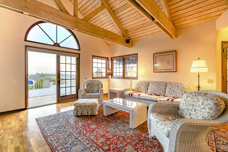 Ljus, öppen och varm vardagsrum med välvt tak och trä royaltyfri fotografi
