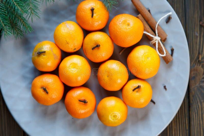Ljus apelsin för tangerin som är mogen med gröna sidor på en grå platta med granfilialer på trätabellen jul som ställer in tabell royaltyfri bild
