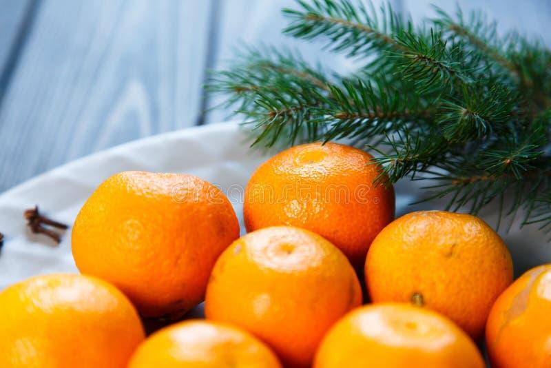 Ljus apelsin för tangerin som är mogen med gröna sidor på en grå platta med granfilialer på trätabellen jul som ställer in tabell arkivbilder