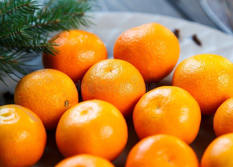 Ljus apelsin för tangerin som är mogen med gröna sidor på en grå platta med granfilialer på trätabellen jul som ställer in tabell arkivfoto