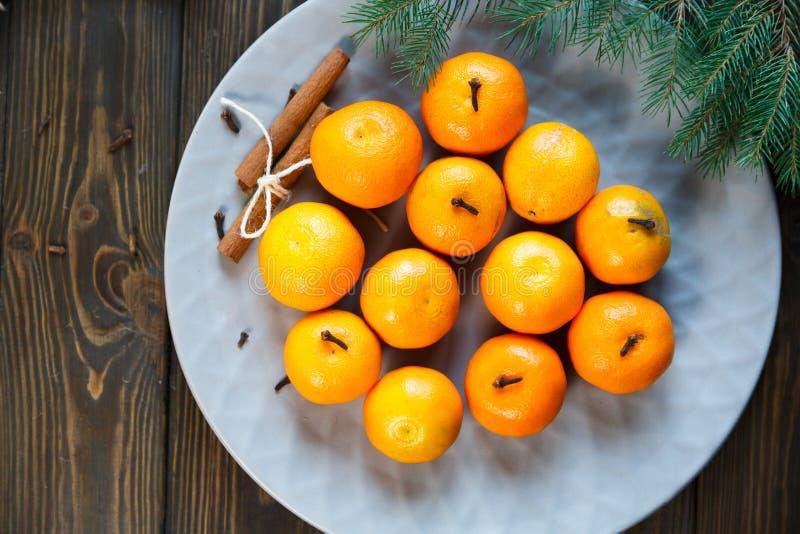 Ljus apelsin för tangerin som är mogen med gröna sidor på en grå platta med granfilialer på trätabellen jul som ställer in tabell arkivbild