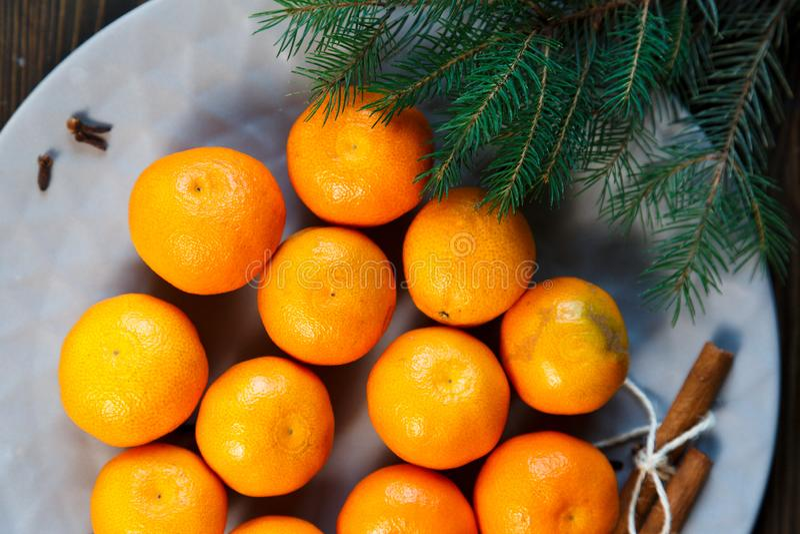 Ljus apelsin för tangerin som är mogen med gröna sidor på en grå platta med granfilialer på trätabellen jul som ställer in tabell royaltyfri fotografi