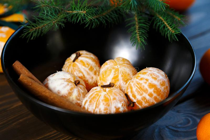 Ljus apelsin för tangerin som är mogen med gröna sidor på en grå platta med granfilialer på trätabellen jul som ställer in tabell royaltyfria foton