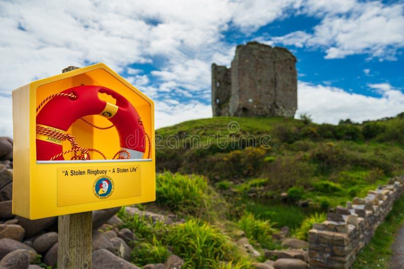 Ljus apelsin som är ringbuoy framme av ett gammalt torn, Irland royaltyfria foton