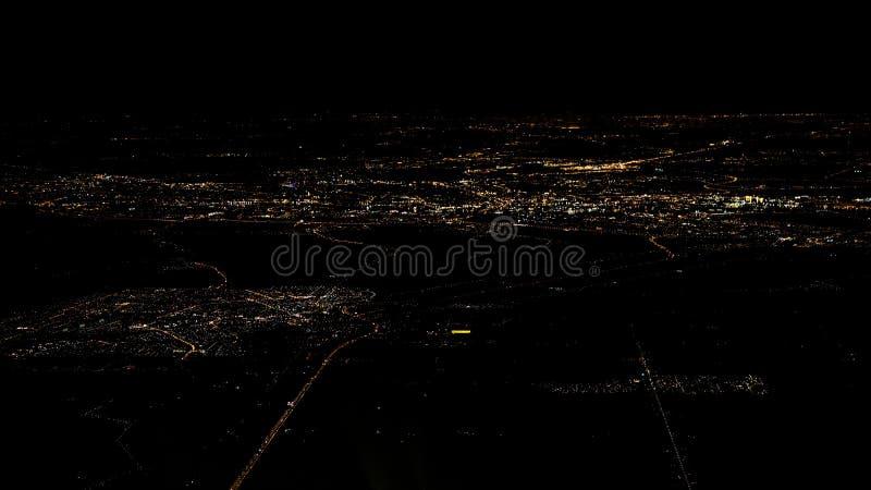 Ljus av den bästa sikten för vägAmsterdam stad från flygplanfönster på natten royaltyfria foton