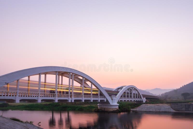 Ljus av drevet på morgonen på den vita bron royaltyfri bild
