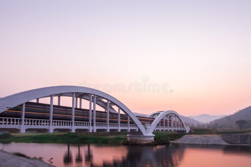 Ljus av drevet på morgonen på den vita bron royaltyfria bilder