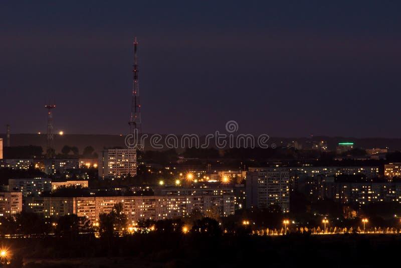 Ljus av nattstaden med ett televisiontorn royaltyfri fotografi