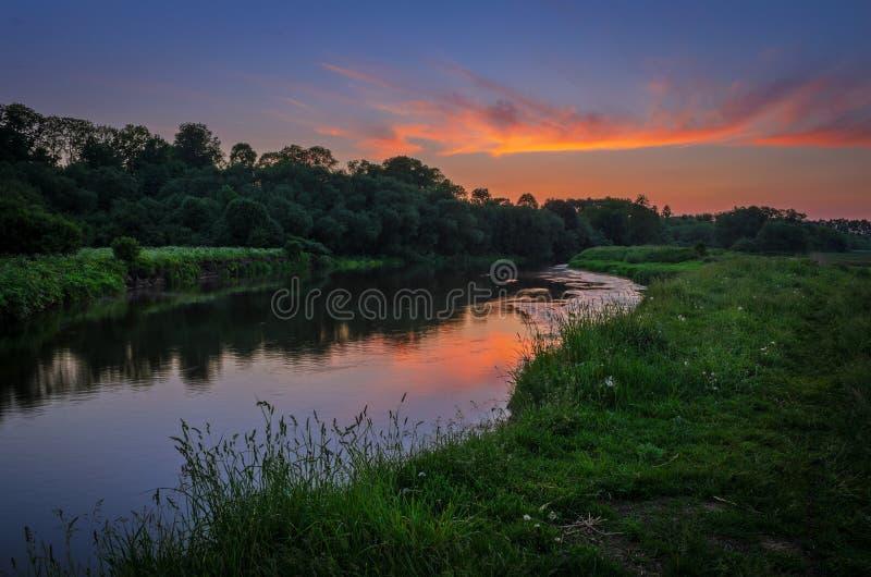 Ljus av solnedgången över floden royaltyfria bilder