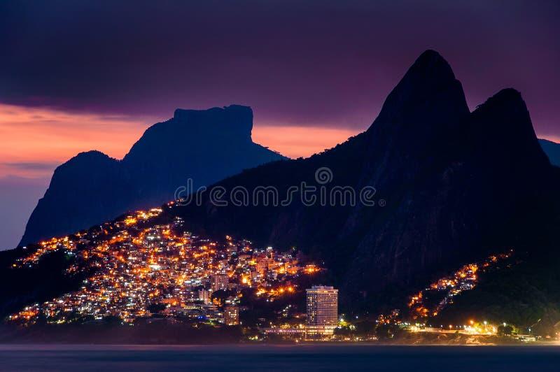 Ljus av Vidigal Favela i Rio de Janeiro, på natten, med berg arkivfoto