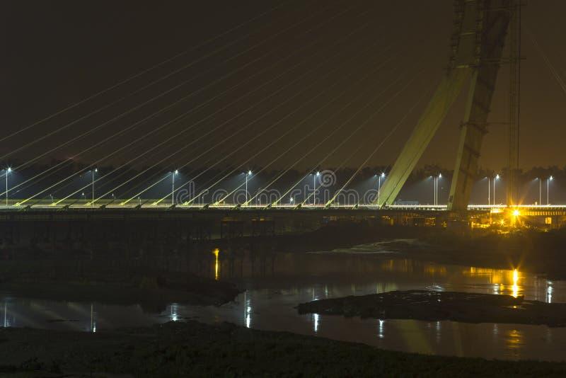 Ljus bakbelyst kabel-bliven bro över den Yamuna floden på natten H?ftebro delhi india royaltyfria foton