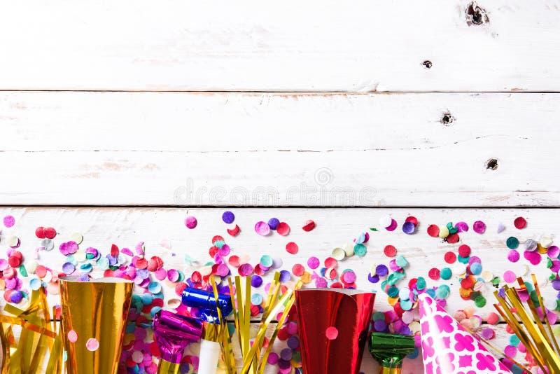 Ljus bakgrund Festa lock och konfettier på vit träbakgrund arkivfoto