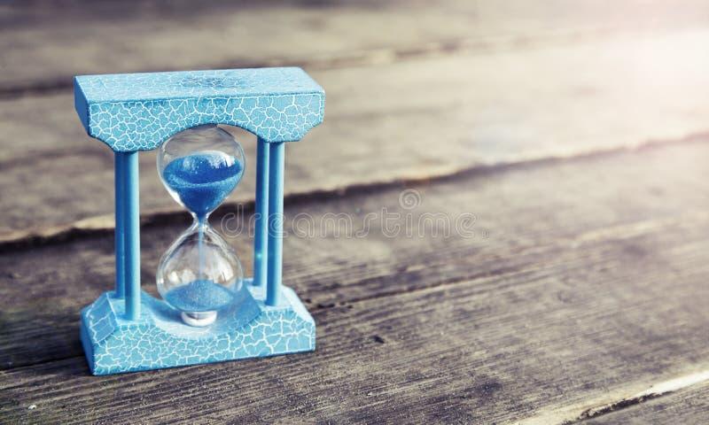 Ljus - blått timglas på träbakgrund, tappningfärgsignal arkivfoton