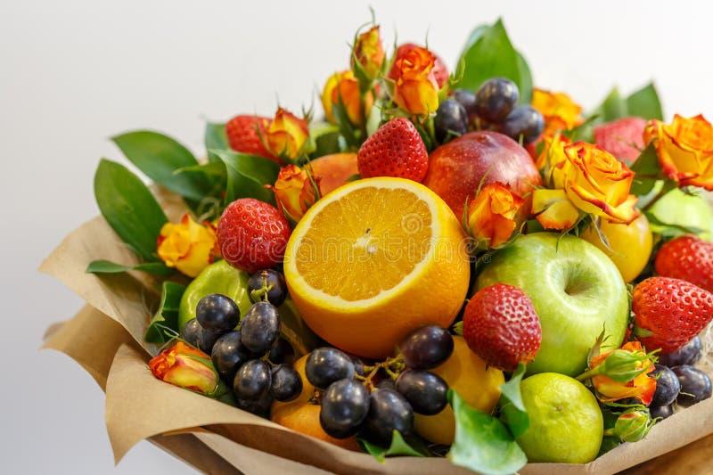 Ljus bukett som består av äpplen, apelsiner, jordgubbar, druvor, plommoner och blommor av trädgårds- rosor som en gåva royaltyfri bild