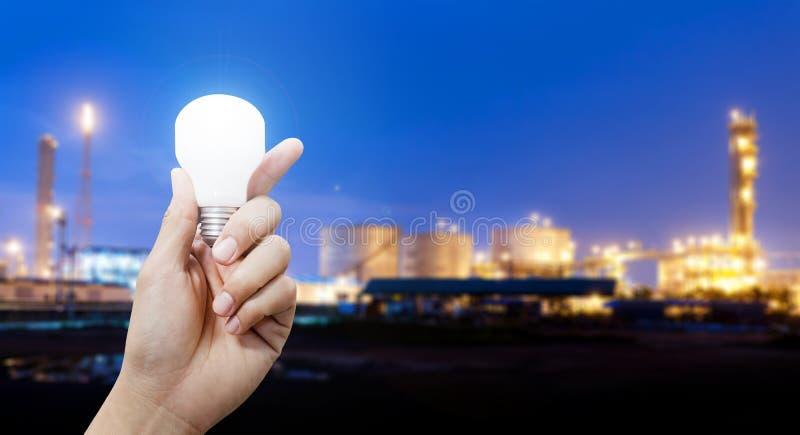 Ljus energi för bransch, hand som rymmer den ljusa kulan i industriellt ämne royaltyfria bilder