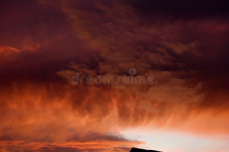Ljus färgrik solnedgång med intensiva moln fotografering för bildbyråer