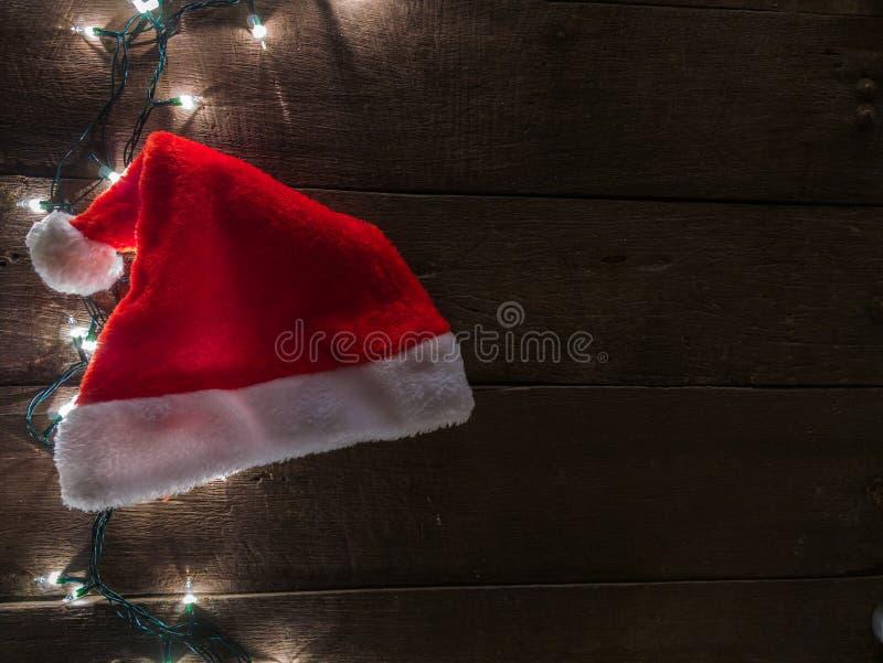 Ljus för jultomten hatt och julpå träskrivbordbakgrund och tömmer utrymme för text Bästa sikt med kopieringsutrymme arkivfoton