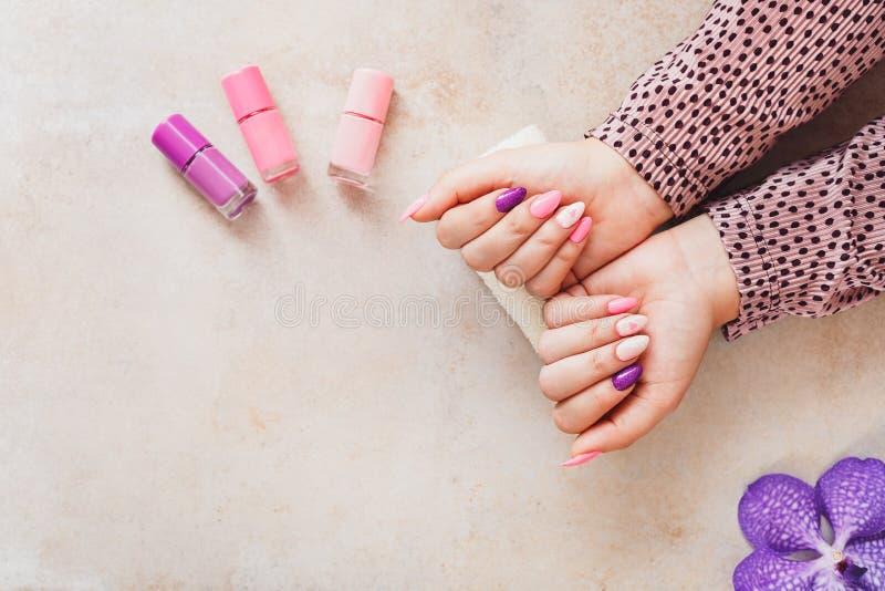 Ljus festlig lila- och rosa färgmanikyr royaltyfri foto