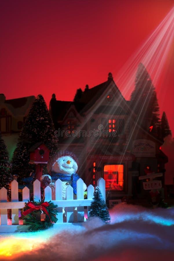 Ljus från stjärnan av Betlehem skiner ner på lycklig framsida för snögubbe` s julminiatyrby arkivfoto