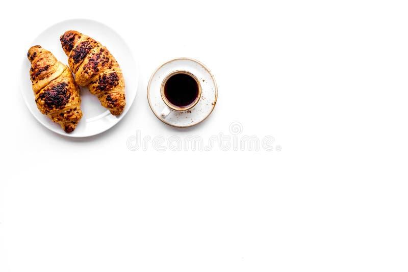 Ljus frukost liten kopp av svart kaffe och gifflet på vit copyspace för bästa sikt för bakgrund royaltyfria bilder