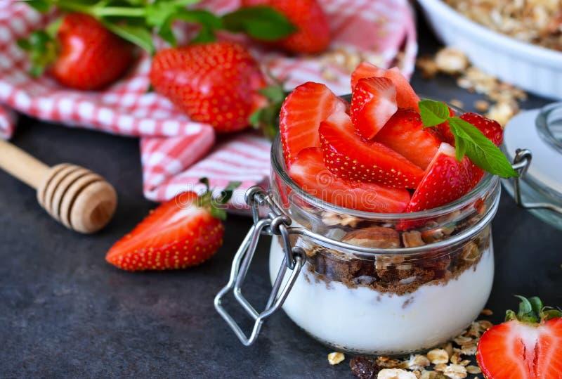Ljus frukostefterrätt med yoghurt, granola och jordgubbar arkivfoto