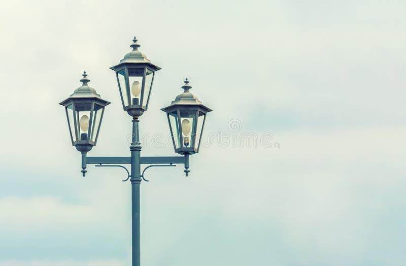 ljus gammal gata Himlen med åskmoln Elektrisk belysning av den moderna staden Härlig tappninglykta royaltyfria bilder
