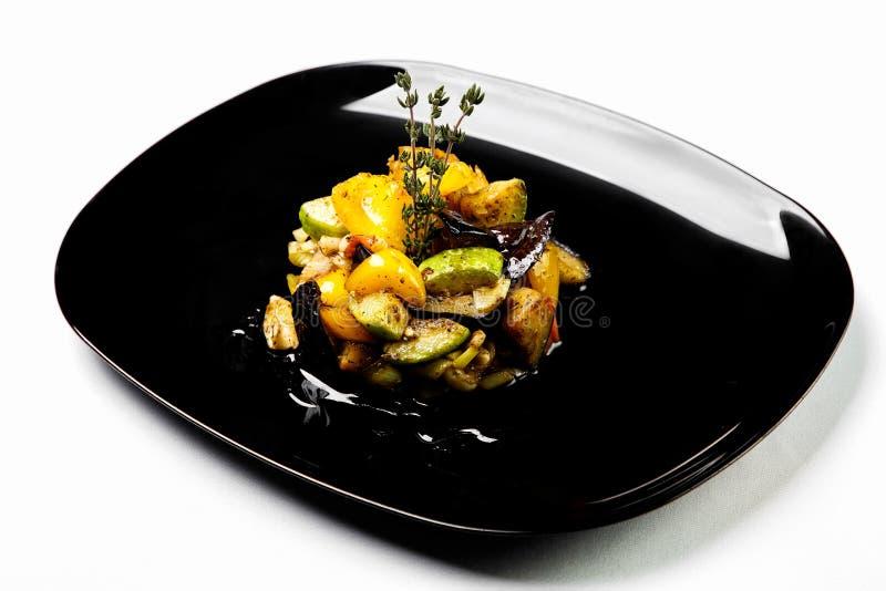 Ljus grönsaksallad som grillas och överträffas med sås på svart pl royaltyfri fotografi