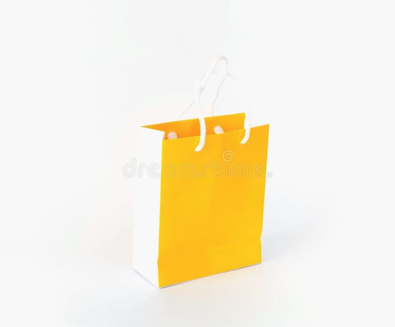Ljus gul pappers- shoppa påse på vit isolerad bakgrund festlig dekor royaltyfri bild