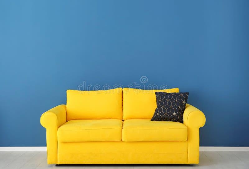 Ljus gul soffa nära väggen fotografering för bildbyråer