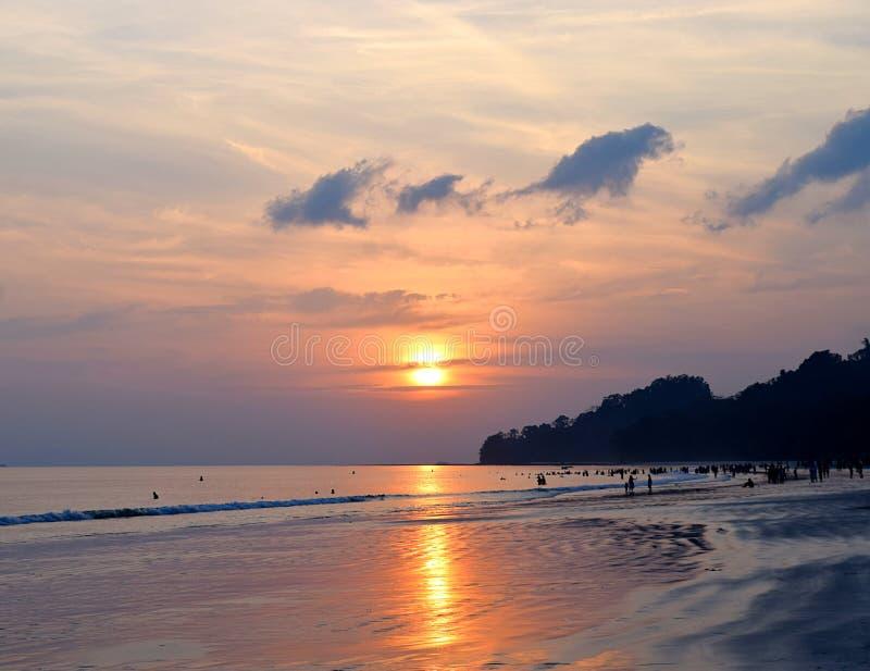 Ljus guld- gul sol som ställer in över havet med färgrik himmel på den fullsatta Radhanagar stranden, Havelock ö, Andaman, Indien royaltyfria bilder