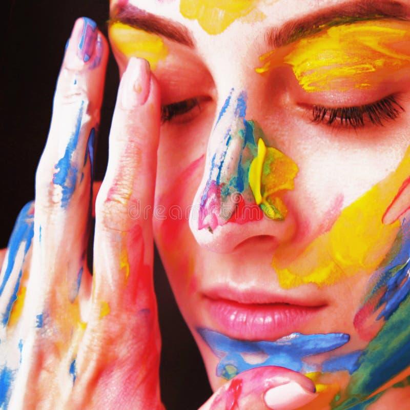 Ljus härlig flicka med färgrikt smink för konst fotografering för bildbyråer