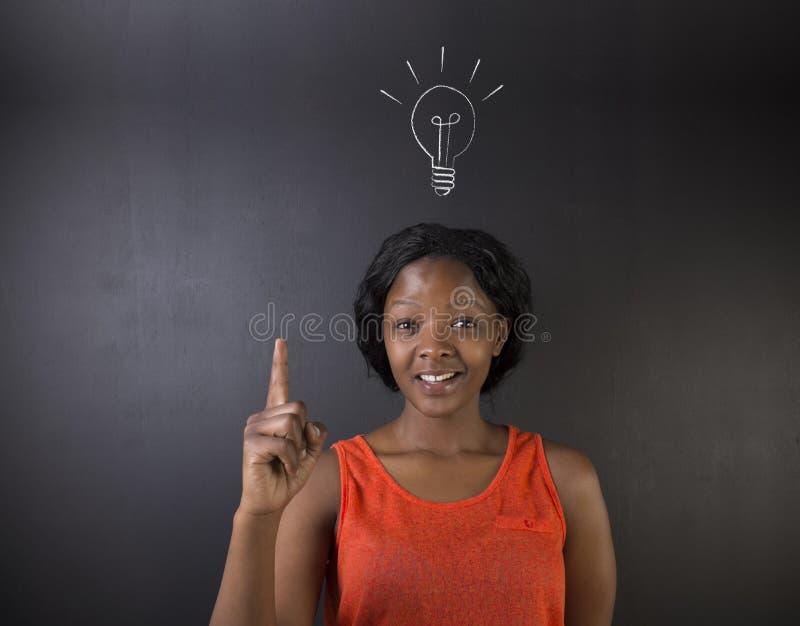 Ljus idélightbulb som söder tänker - afrikan eller afrikansk amerikankvinnalärare eller student royaltyfri fotografi