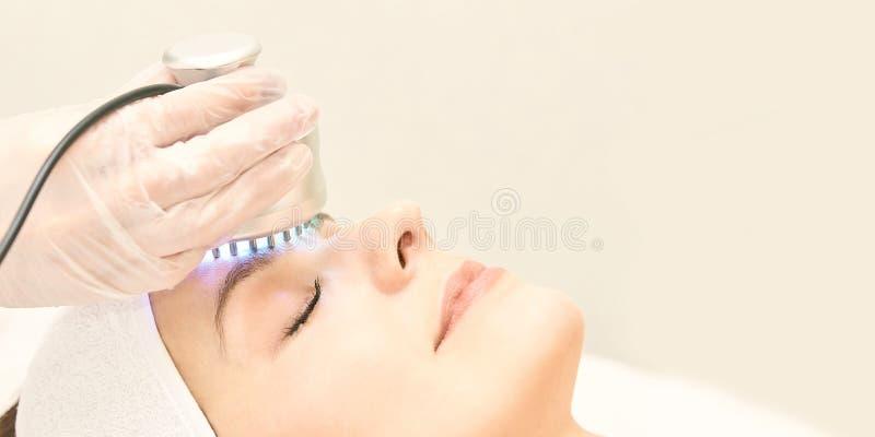 Ljus infrar?d terapi Cosmetologyhuvudtillv?gag?ngss?tt kvinna f?r smink f?r sk?nhetframsidamode Kosmetisk salongapparat Ansikts-  royaltyfri foto
