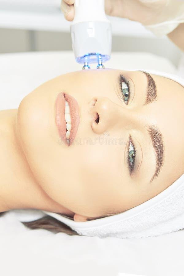 Ljus infrar?d terapi Cosmetologyhuvudtillv?gag?ngss?tt kvinna f?r smink f?r sk?nhetframsidamode Kosmetisk salongapparat Ansikts-  royaltyfria foton