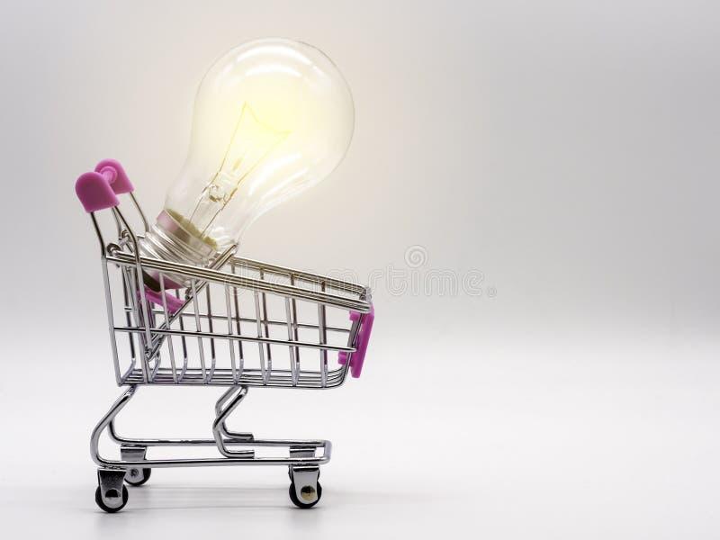 Ljus kula i den shoppa vagnen på vit bakgrund Sparande energi och affärsidé royaltyfria foton