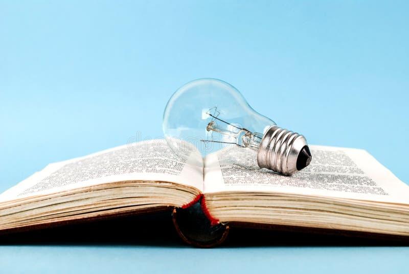Ljus kula på den öppna boken som isoleras på en blå bakgrund arkivbilder