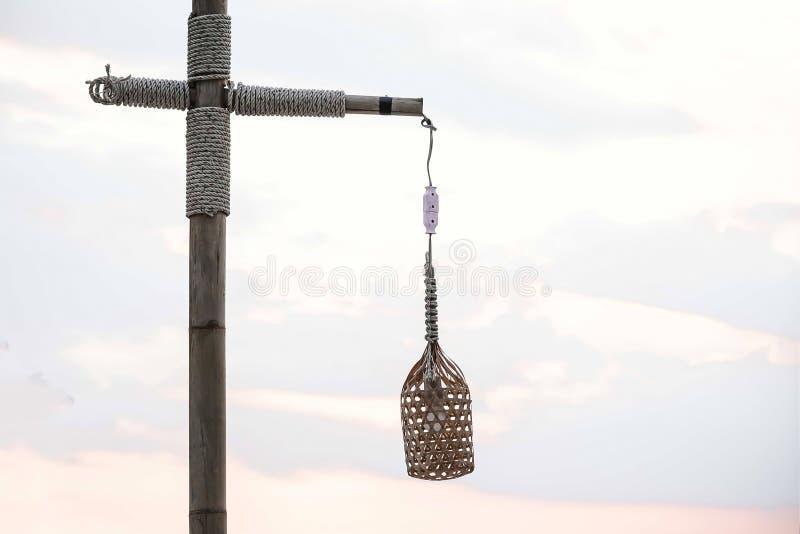 Ljus kula på tråden I lampan Hänga på stranden, mot solnedgånghimlen på en pol av bambu som binds med ett rep arkivfoto