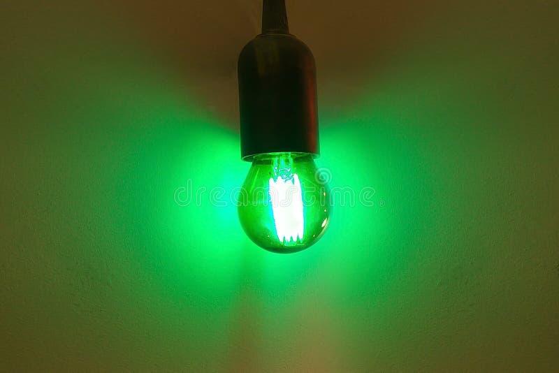 Ljus kula som glöder grön på grå väggbakgrund arkivfoton
