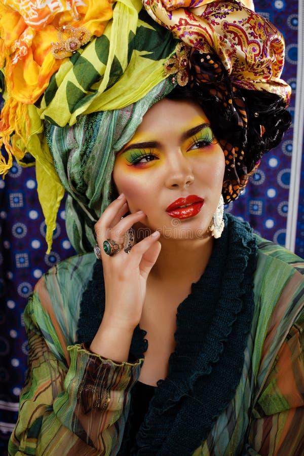 Ljus kvinna för skönhet med idérikt smink, många sjalar på huvudet arkivfoto
